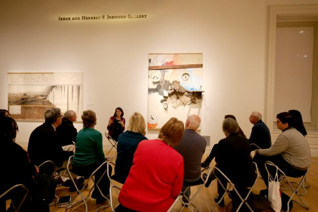 A photograph of a group in the museum sitting and discussing a painting.
