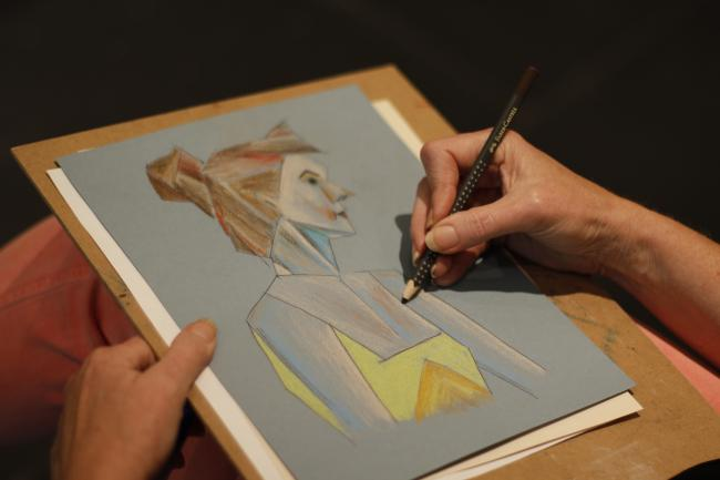 A photograph of hands drawing on a notepad an image of a woman.