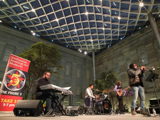A photograph inside the Smithsonian American Art Museum's Kogod Courtyard at night with musicians playing on a stage.