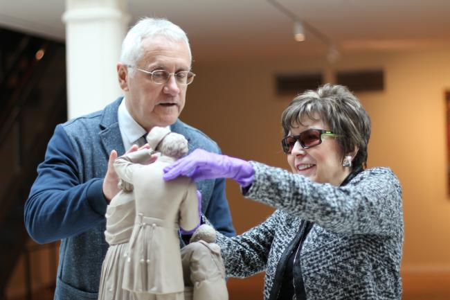 A photograph taken inside the museum of a blind lady with gloves touching a replica of a sculpture.
