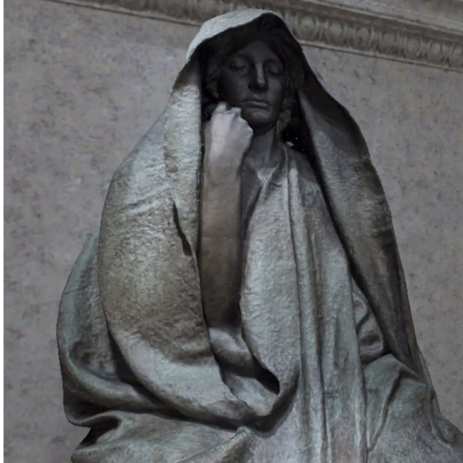 A sculpture of a woman sitting down with her hand on face and a cloth over her head.