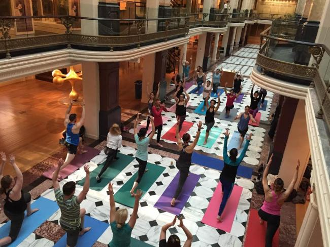 An image inside the Luce Foundation Center with people practicing yoga on the ground floor.