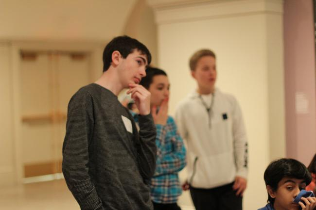 A group of teens looking and pondering at something.
