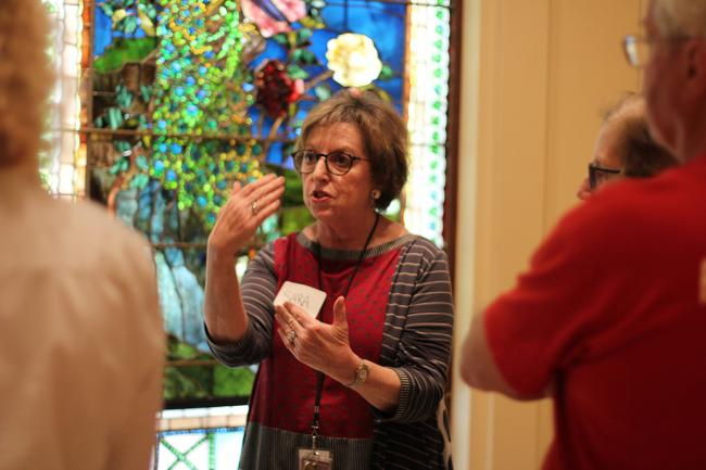 A photograph of a woman talking to a group of people in front of some stained glass.