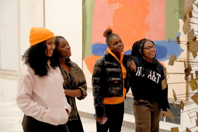 A group of four girls looking at artwork