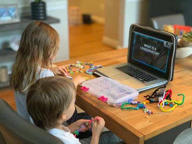 Two children sitting down and participating in a zoom activity