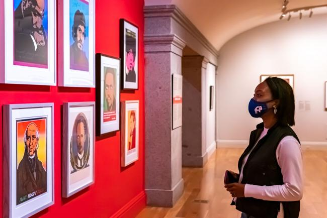 A woman stands in front of a red wall showing 7 graphic artworks