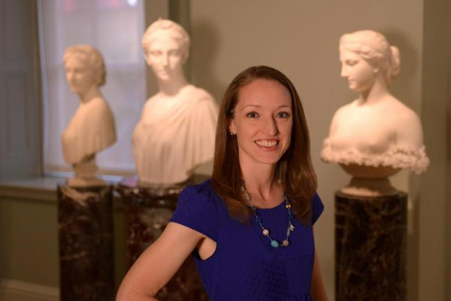 A photograph of a woman standing in an art gallery with busts behind her.