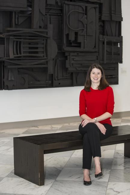 A photograph of a woman sitting down on a bench in a gallery with a red sweater on and a black artwork behind her.