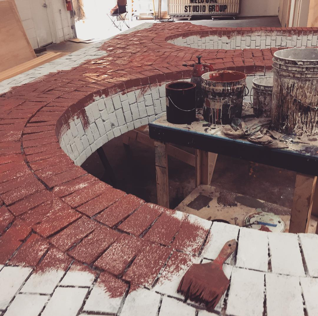 Photo of a faux brick archway being painted red