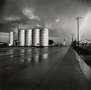 A photograph of a grain elevator in a lightning storm.