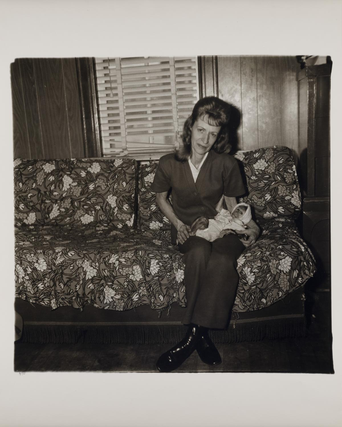 """A black and white photograph by Diane Arbus titled """"Mrs. Gladys 'Mitzi' Ulrich with the baby, Sam, a stump-tailed macaque monkey"""""""