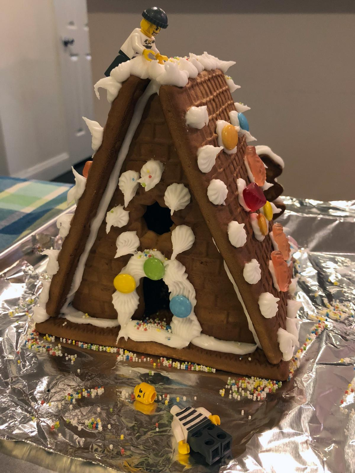 Gingerbread house with candy decorations and two LEGO figures.
