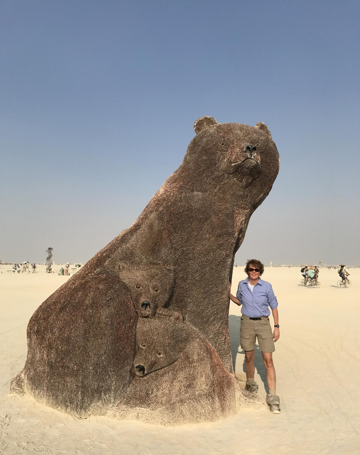 This is a photograph of Stephanie Stebich standing next to the Ferguson's Ursa Mater at Burning Man.