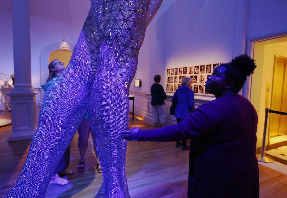 A picture of a woman touching the legs of a large sculpture piece at the Renwick Gallery.