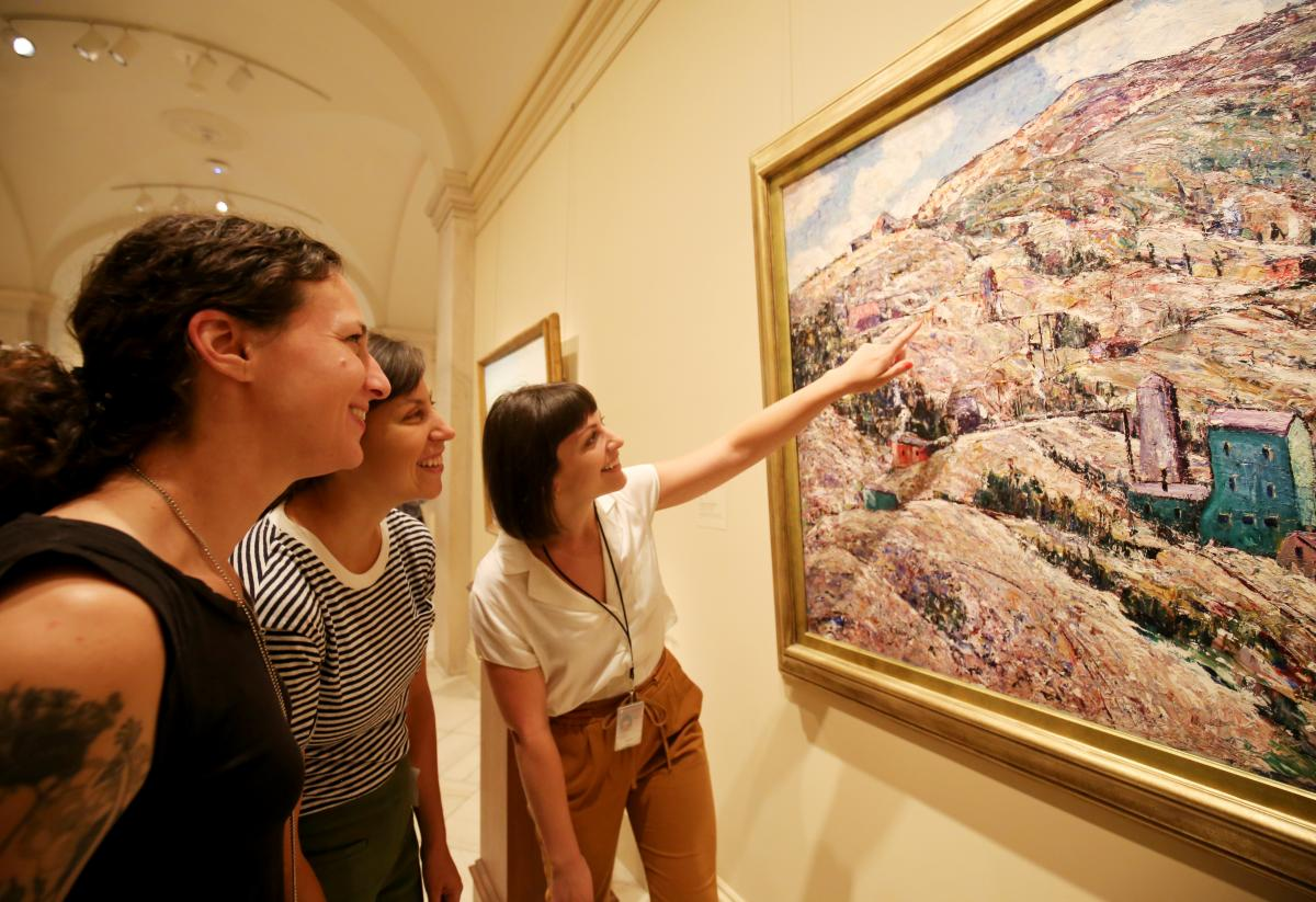 An image of three women looking at a piece of artwork.