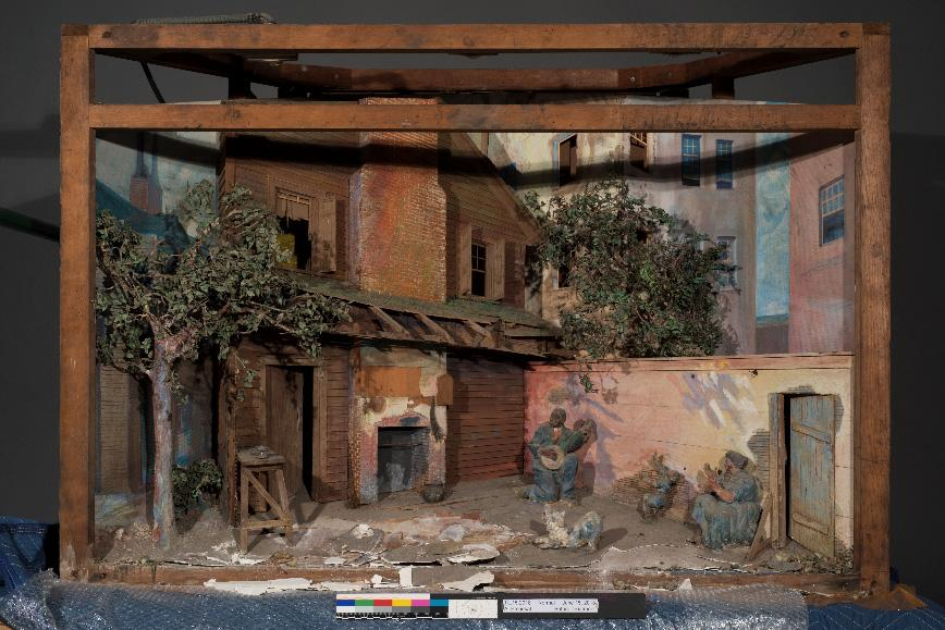This is a photograph of a diorama with a house and man playing guitar outside with his family.