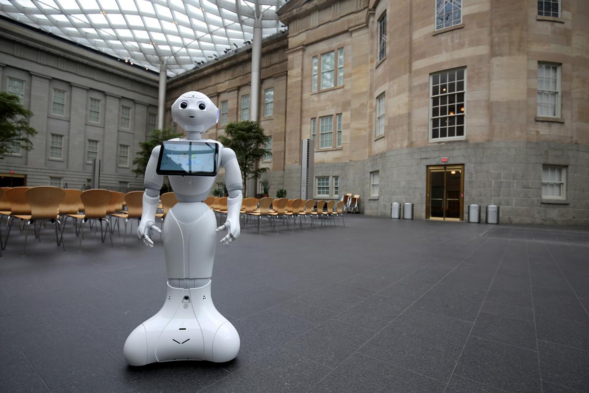 A photograph of Pepper the Smithsonian Robot dancing inside the Smithsonian American Art Museum.