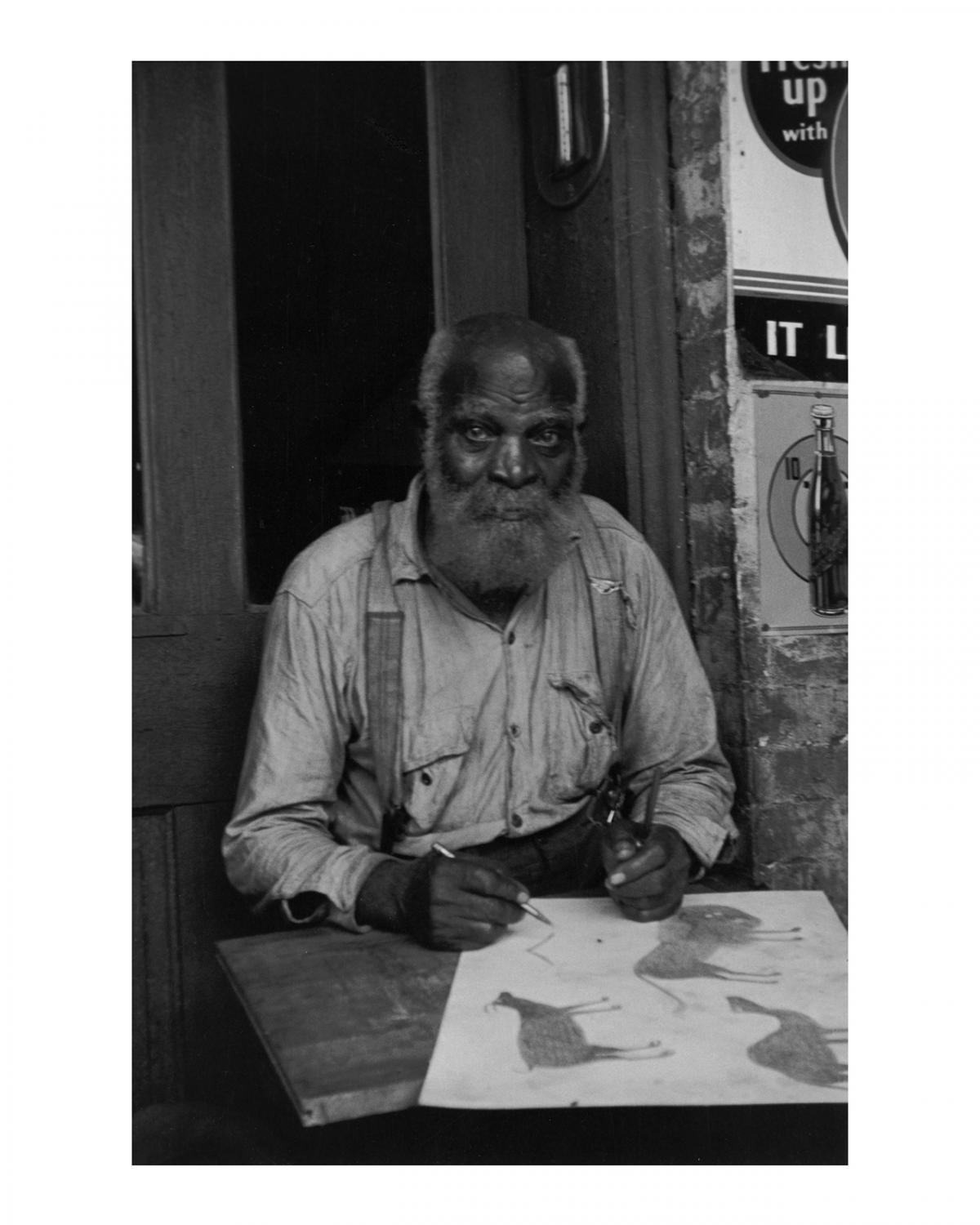 This is an image of artist Bill Traylor sitting at a table.