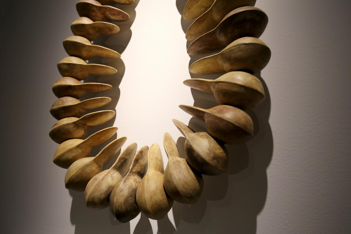 A photograph of the artwork, Ripened Banana, a large scale tan beads in the form of a necklace.