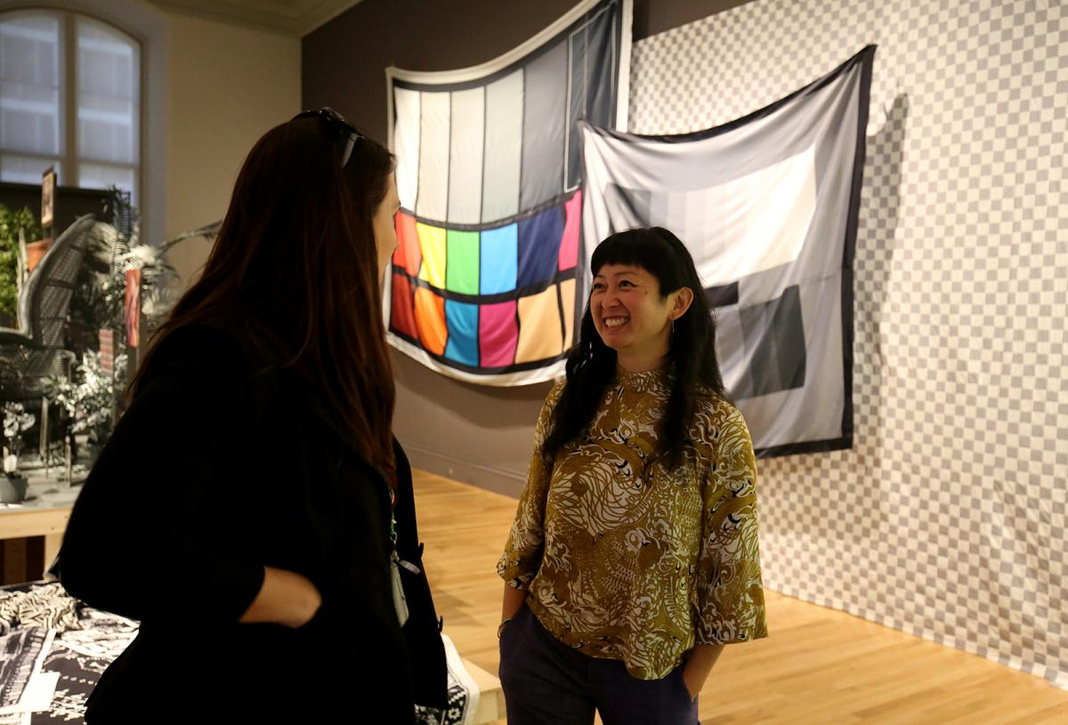 Two women talking to each other inside an art gallery.