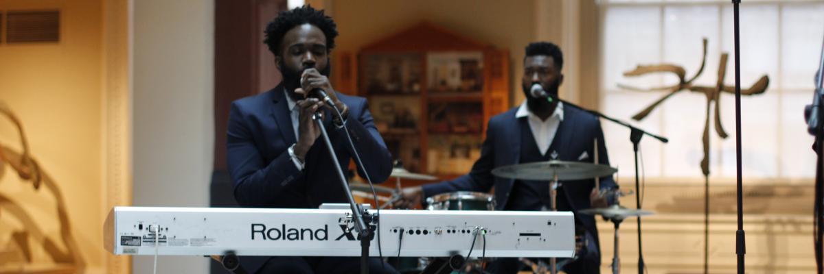 A man playing at a piano and a drummer behind him.