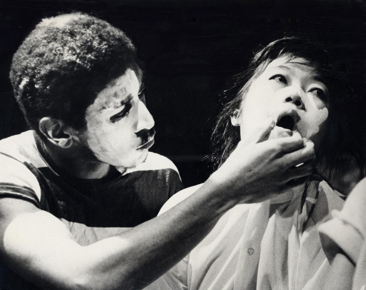 A photograph of a man holding a woman's mouth open.