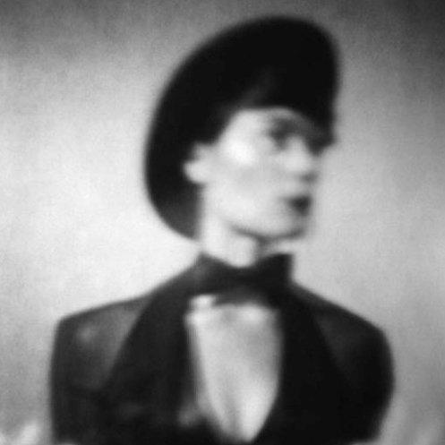 An evocative black and white photo of performer Jax Deluca in bowtie, hat, and tux.
