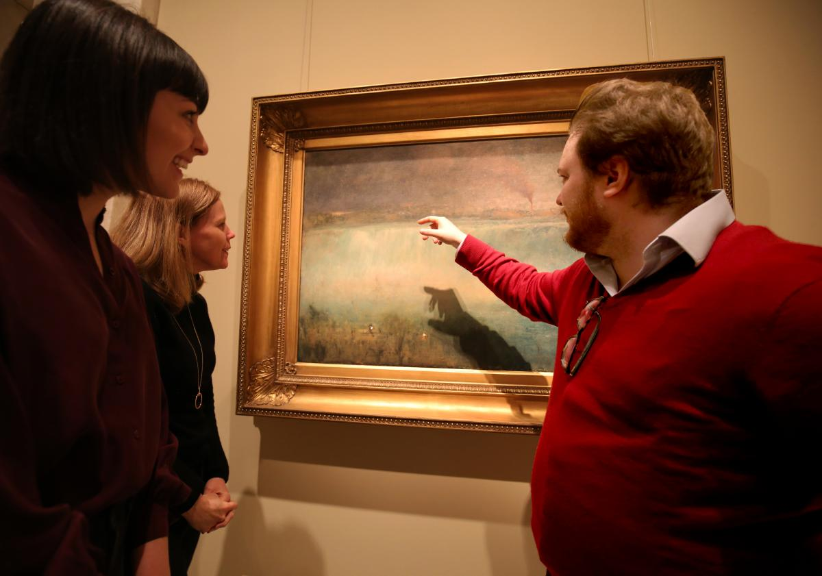 A photograph of a man in a red sweater pointing to a painting of Niagra Falls as others watch.