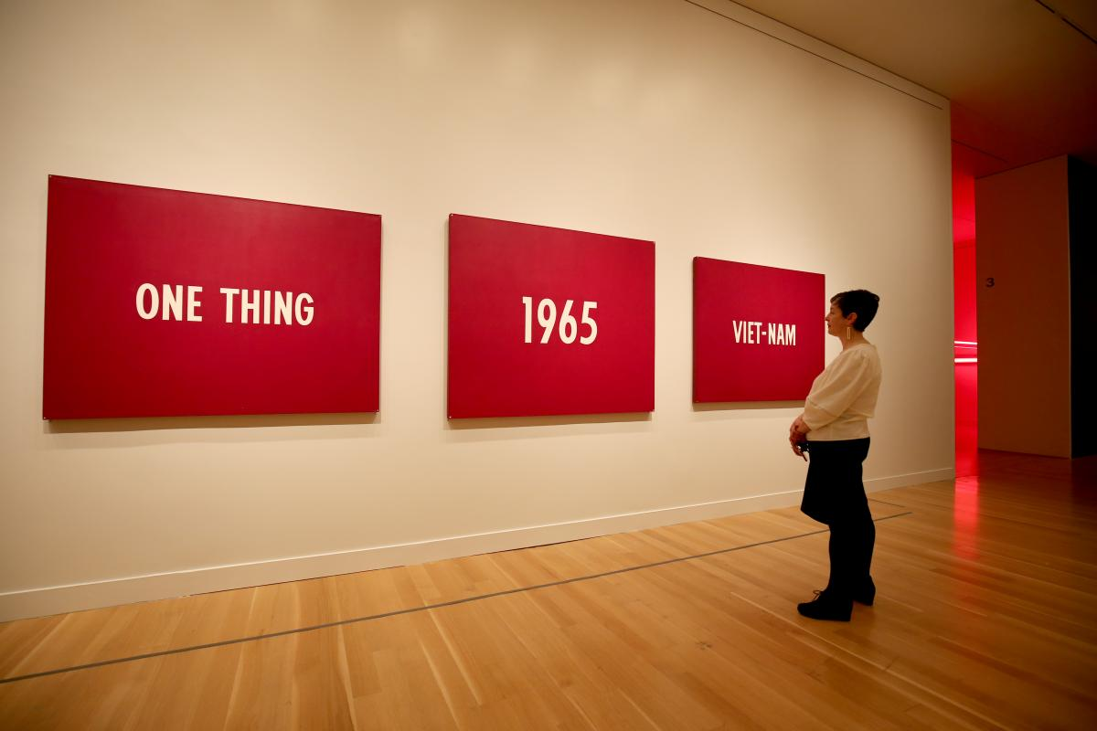"A photograph of a woman standing in front of a three piece painting that says ""One Thing, 1965, Viet Nam"""