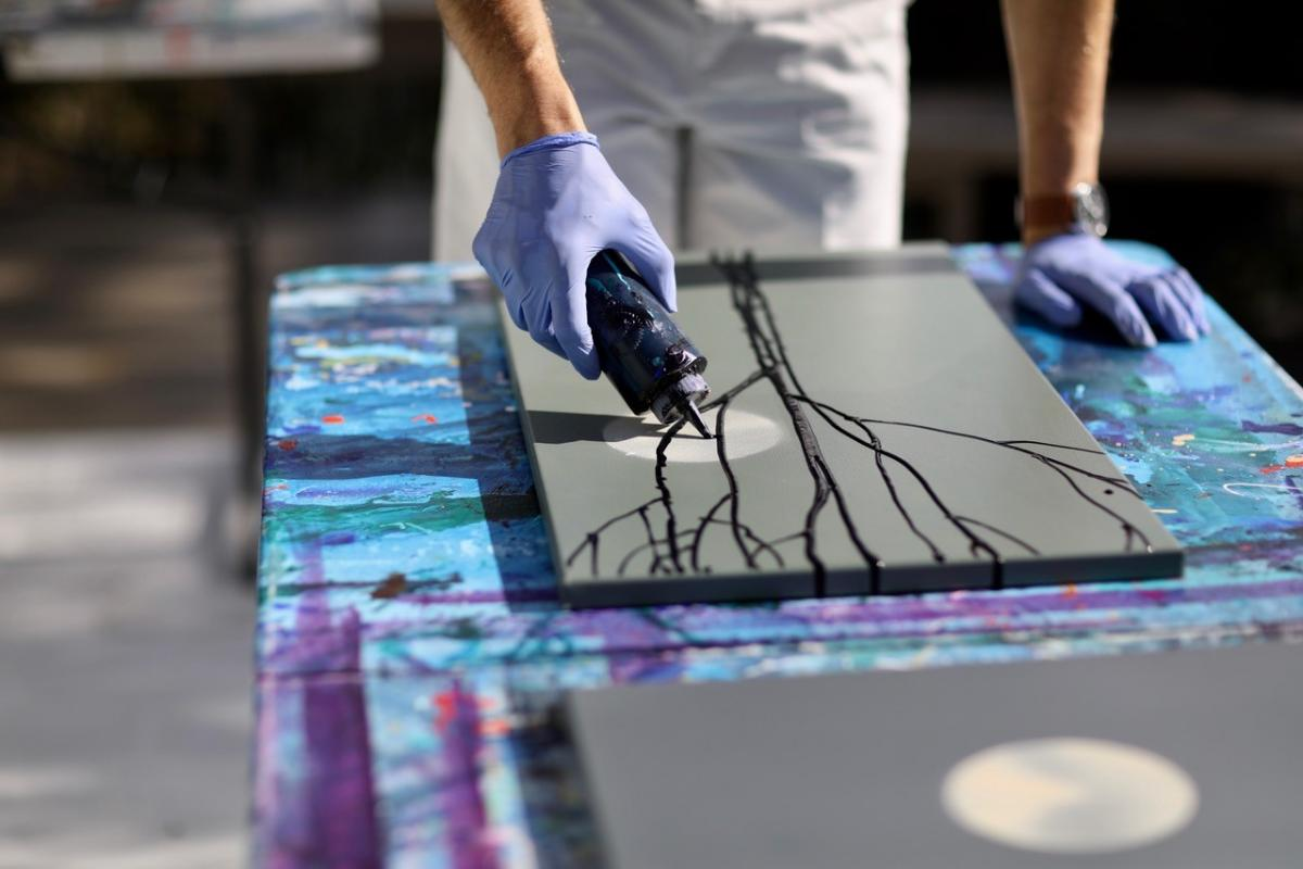 A detailed photograph of a hands on a table working on a painting.