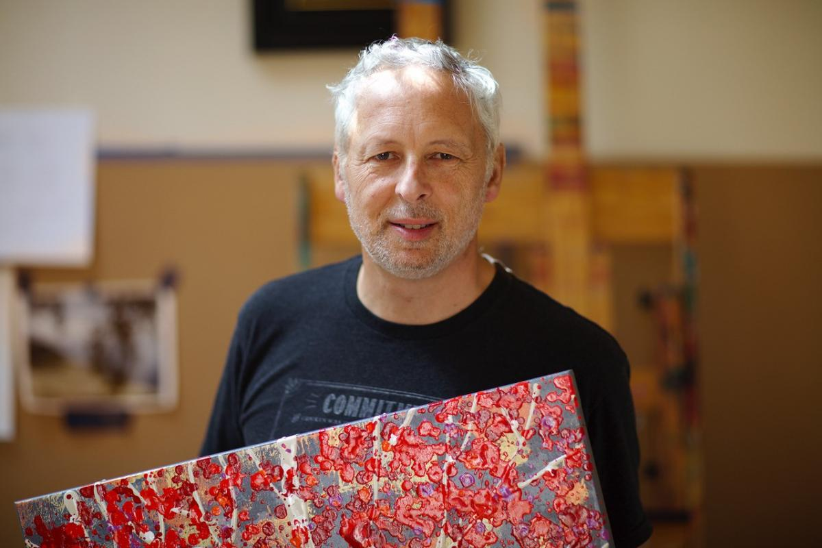 A photograph of a man holding a red painting.