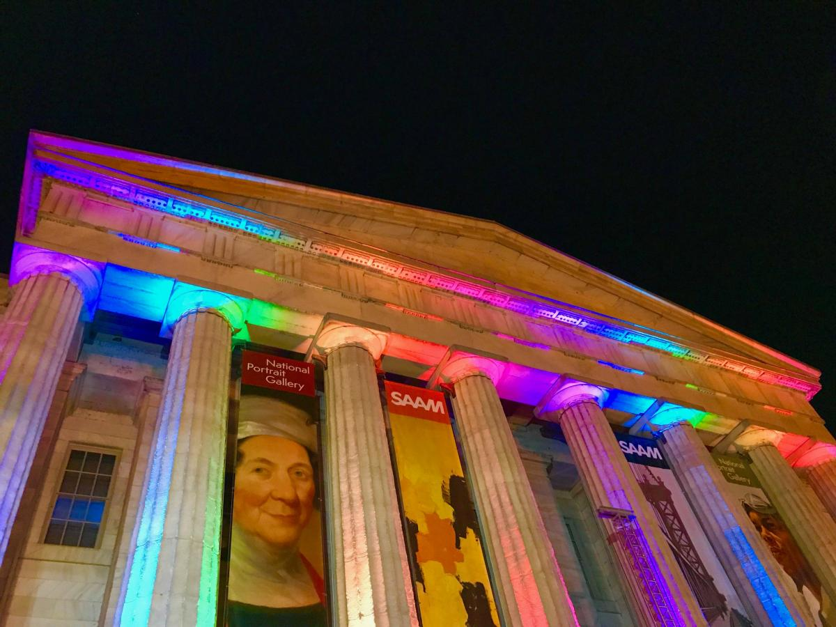 A photograph of the outside of the Smithsonian American Art Museum at night with rainbow lights shining on the building.