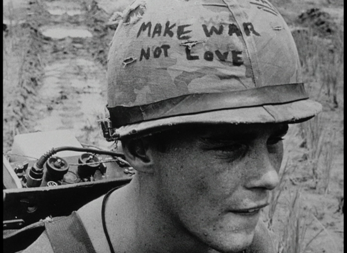 "The face of soldier with a helmet that says ""make war not love"""