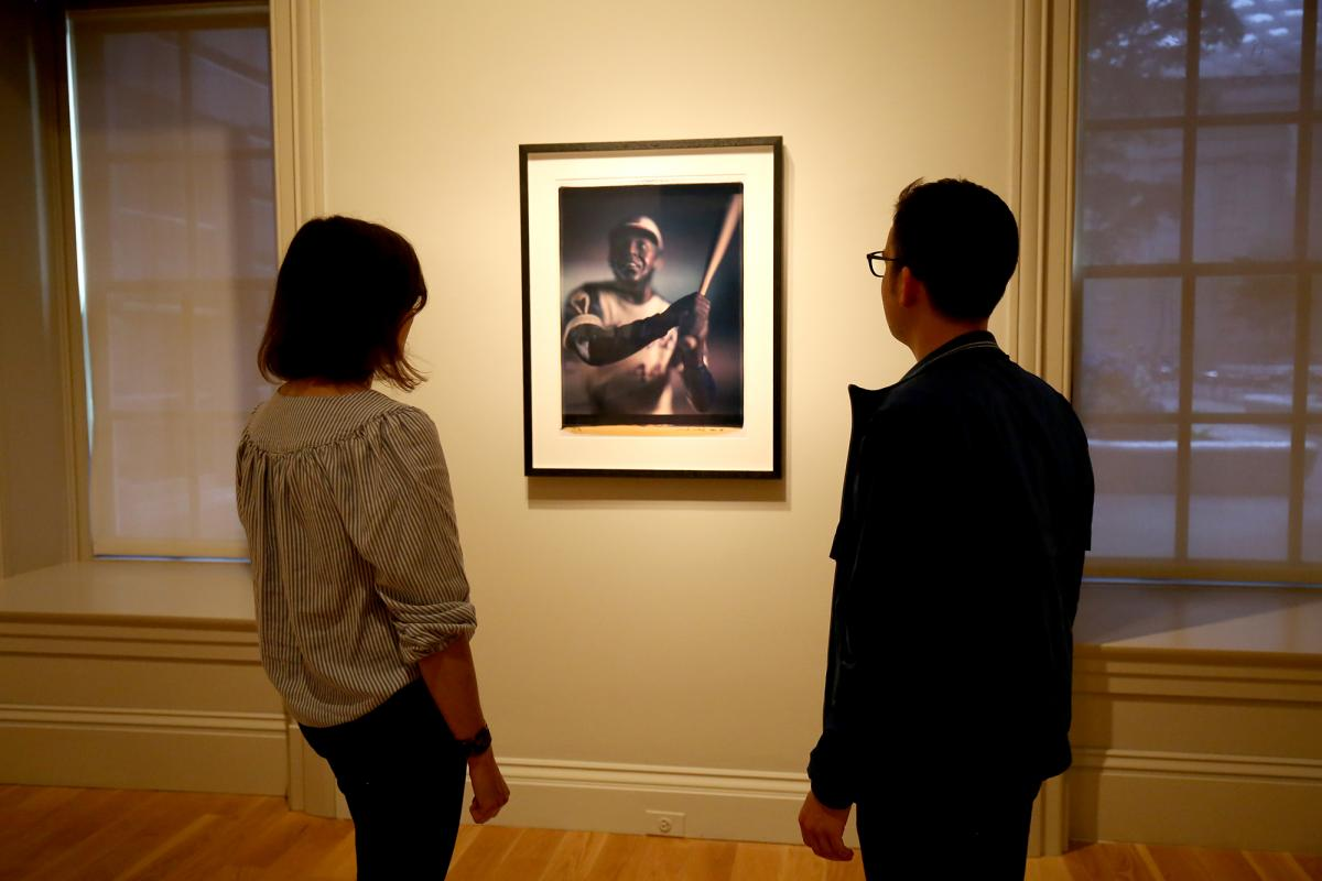 A photograph of two people looking at a piece of artwork on a wall.
