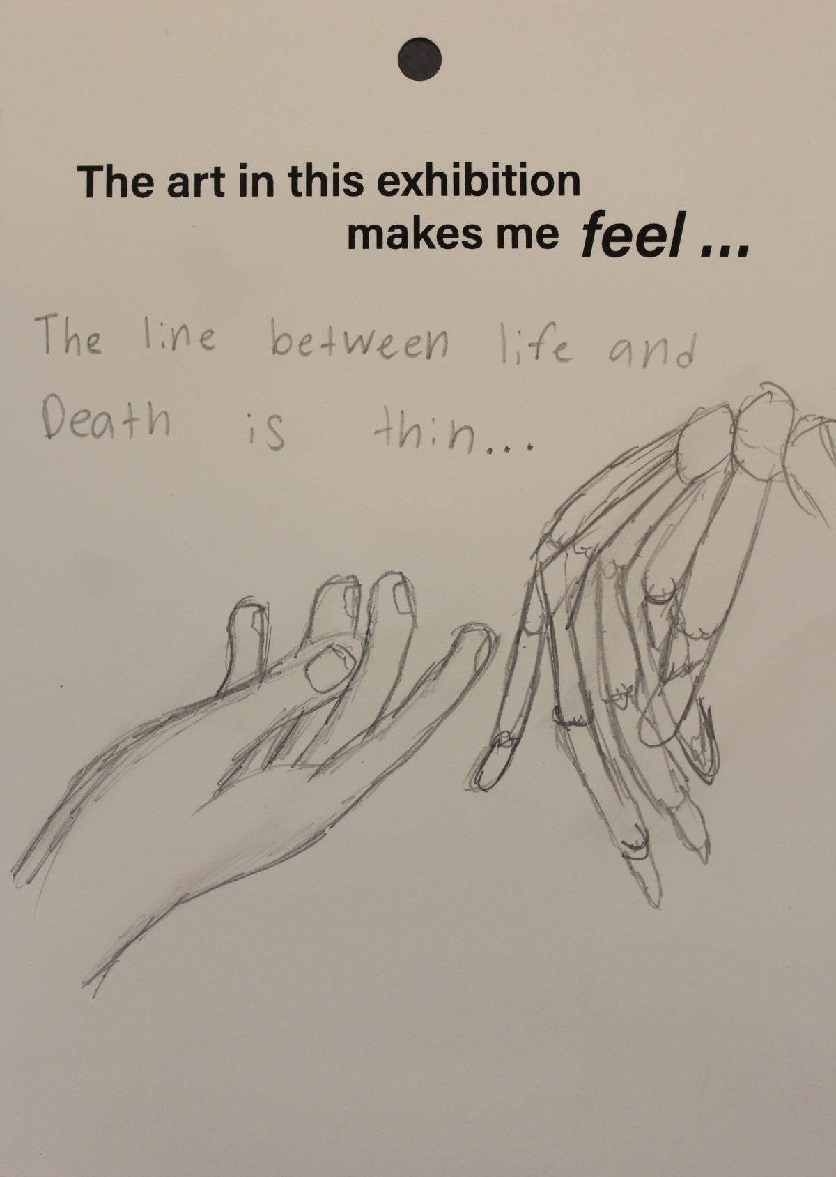 A visitor draws a hand and a skeletal hand