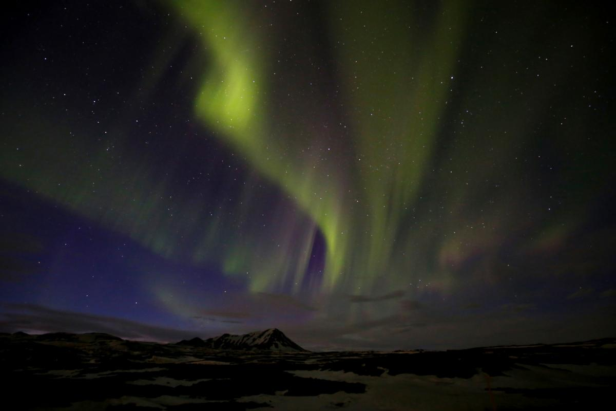 A photograph of a mountain with green northern lights overhead.