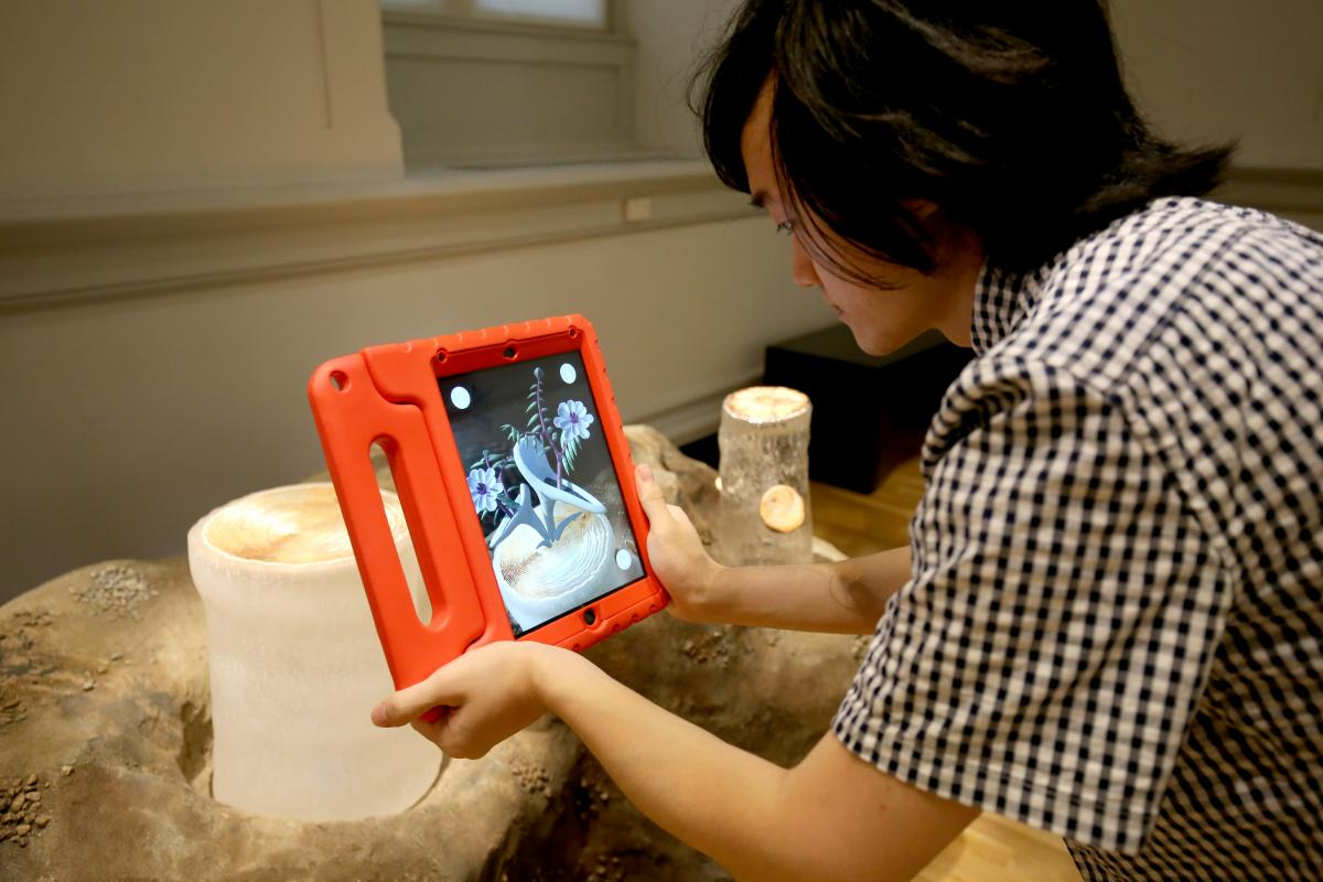A photograph of a male holding an ipad in front of Ginny Ruffner's artwork.