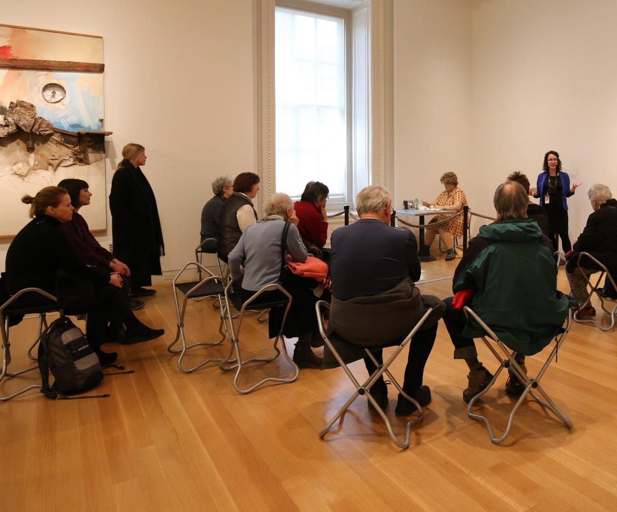 A research fellow talks to an audience about Duane Hanson's Woman Eating