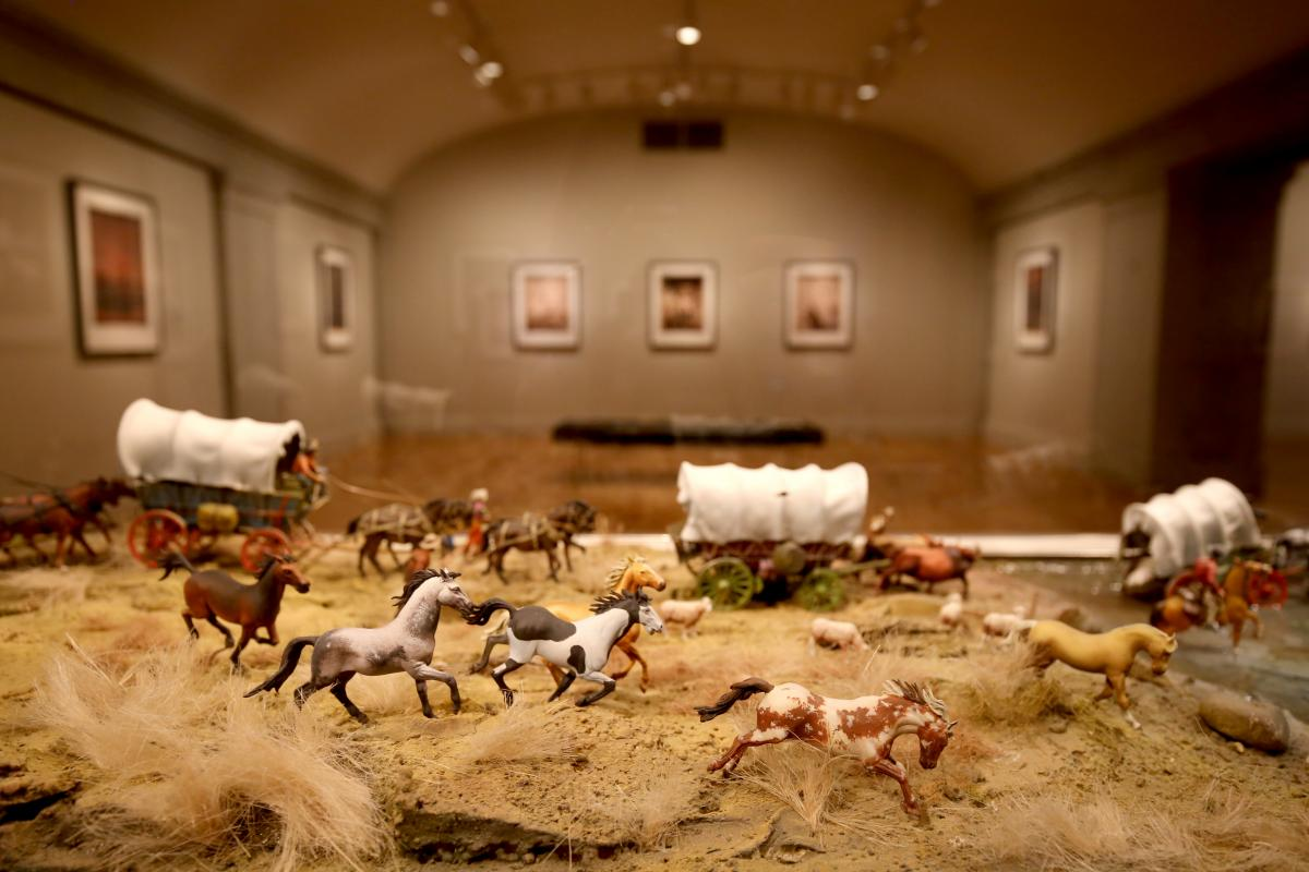 A photograph of an installation of toy figurines in a wild west landscape.