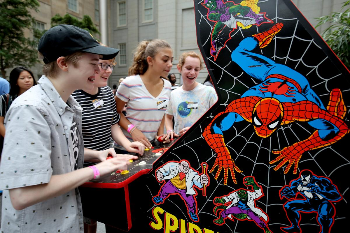A photograph of four teenagers playing a spider man video game.