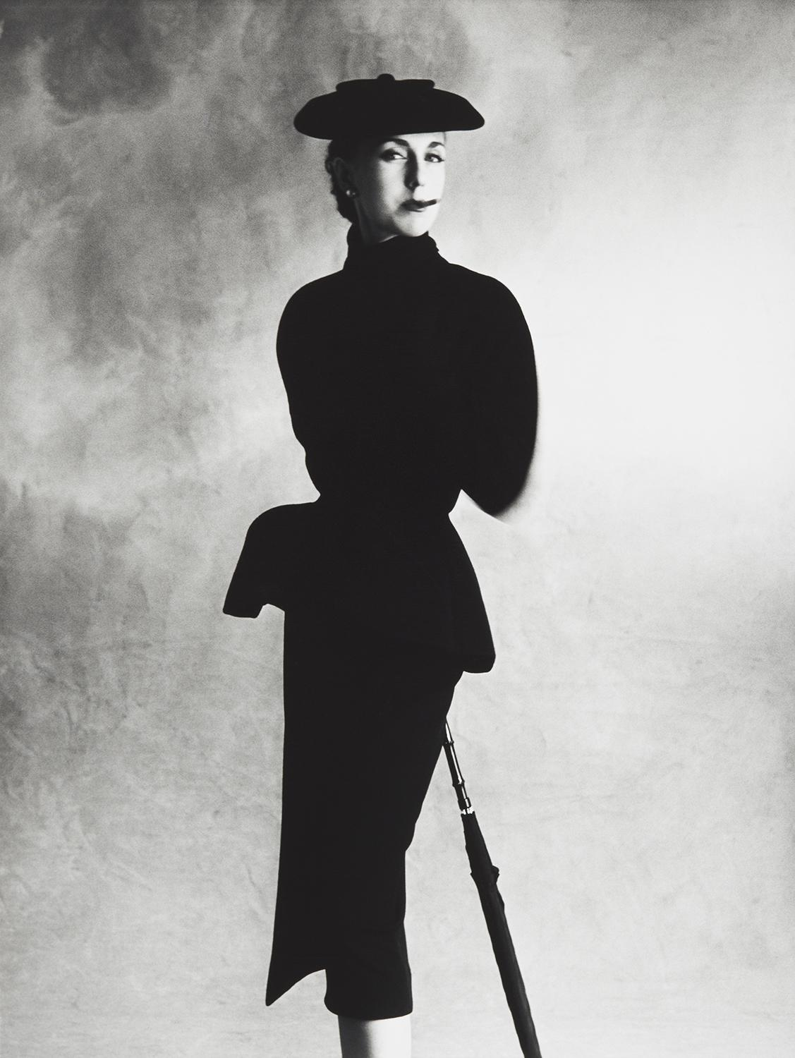 A woman standing in a black suit with a black hat.