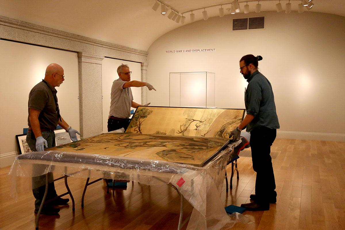 Three men unpacking a silk screen.