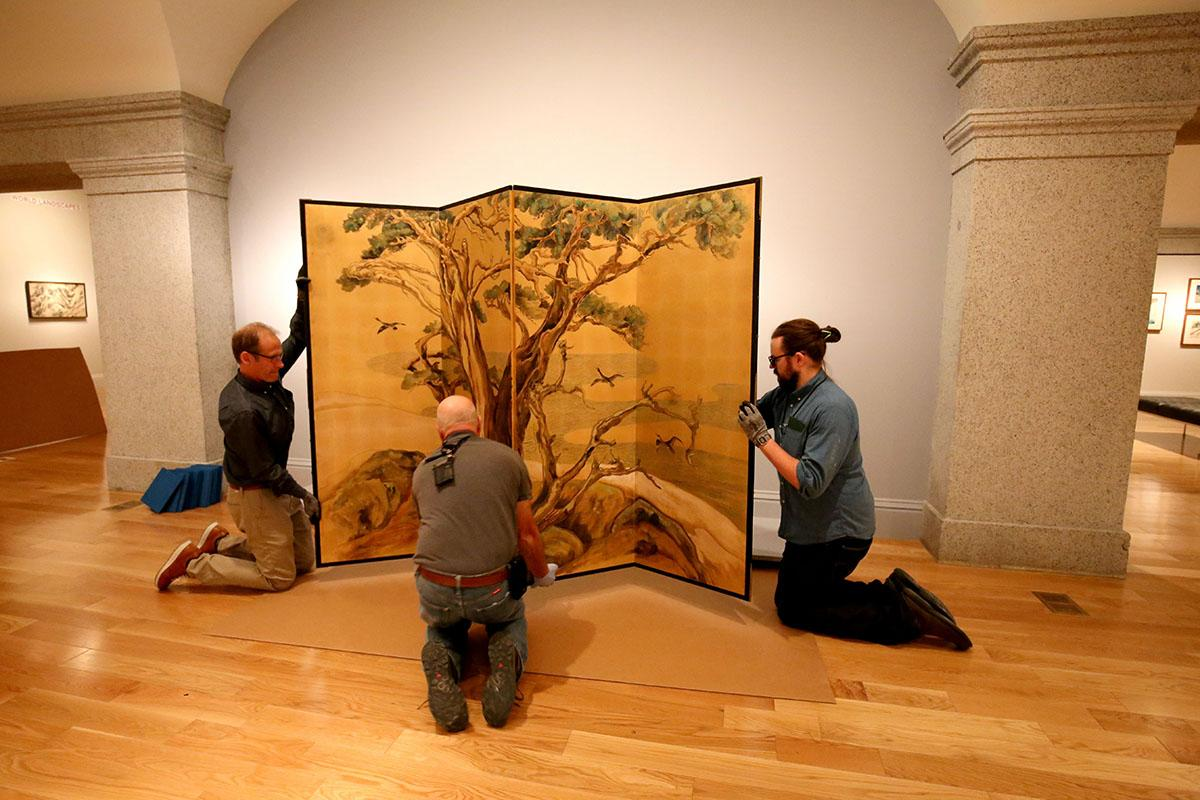 Three men installing a silk screen.