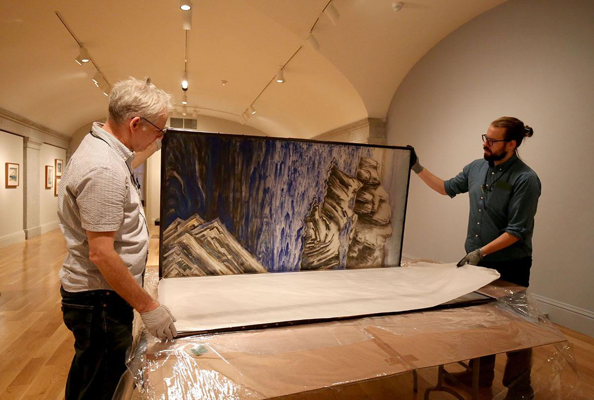 A photograph of two men unpacking a silk screen.