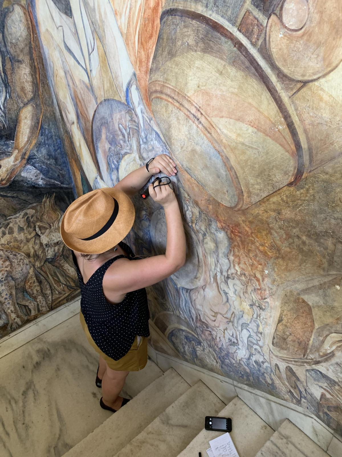 SAAM conservator Gwen Manthey examining a mural for damage