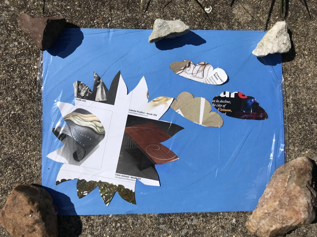 A photo of shapes cut out on a piece of paper with rocks holding it down.