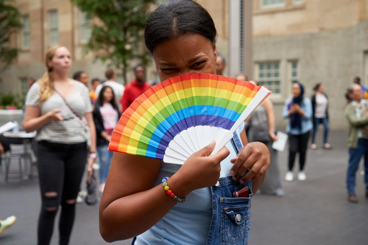 A photograph of a figure with a rainbow fan