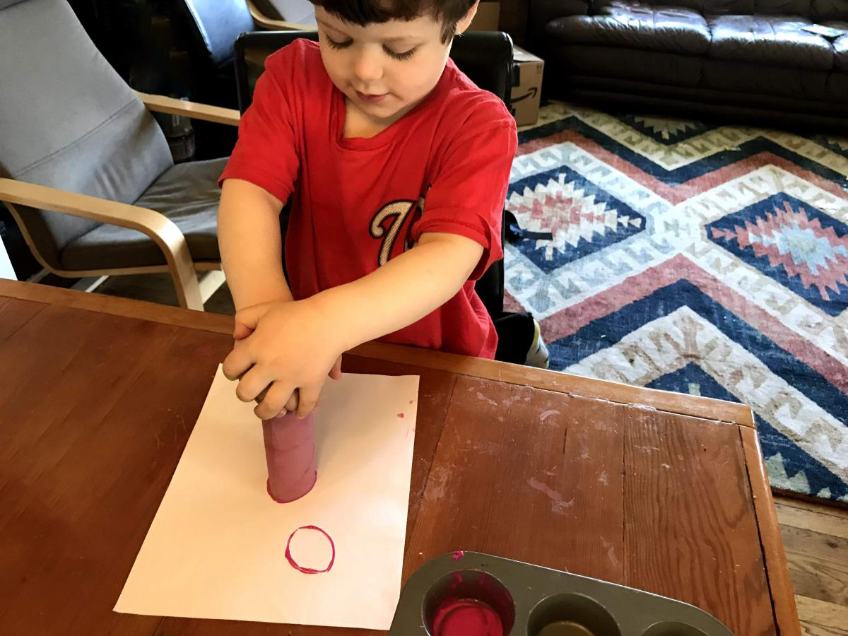 A photograph of a child making a stamp flower with a paper towel roll.