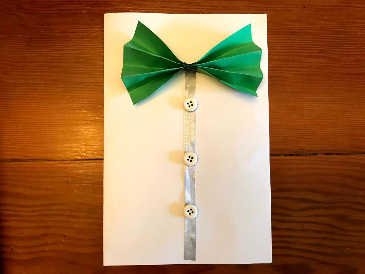 A photograph of a handmade card with a bowtie